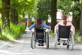 Two women on wheelchairs in park — Stock Photo