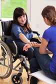 Girl on wheelchair talking with female friend — Stock Photo