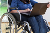 Handicapped woman on wheelchair using laptop — Stock Photo