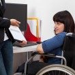 Woman on wheelchair analyzing charts with her boss — Stock Photo #49423825