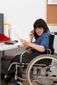 Disabled young girl on wheelchair working in her office — Stock Photo