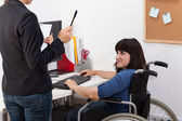 Disabled woman on wheelchair talking with manager — Stock Photo