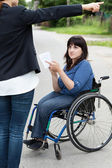 Woman on wheelchair asking a passerby about directions — Stock Photo