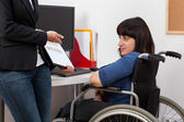 Woman on wheelchair analyzing charts with her boss — Stock Photo