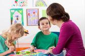 The teacher helps children  — Stock Photo