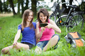 Girls with smartphone on a glade — Stock Photo