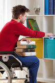 Disabled holding a book and wiped the dust — Stock Photo