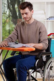 A disabled man sitting and ironing shirt — Stock Photo