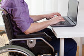 Disabled working on laptop — Stock Photo