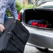 Man putting suitcases in car trunk for a journey — Stock Photo #49666183