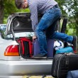 Man using his strength to packing luggage into car — Stock Photo #49666213