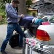 Man pushing luggage into trunk of his car — Stock Photo #49666215