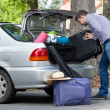 Man trying to putting a travel bags into a car — Stock Photo #49666281