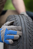 Mechanic hands and car tire — Stock Photo