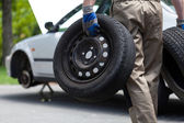 Mechanic holding a two car wheel  — Stock Photo