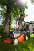Man cutting grass in his yard — Stock Photo