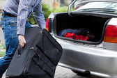 Man putting suitcases in car trunk for a journey — Stock Photo