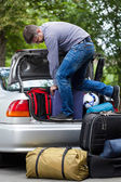 Man using his strength to packing luggage into car  — Stock Photo