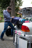 Man pushing luggage into trunk of his car — ストック写真