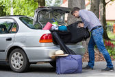 Man trying to putting a travel bags into a car — Stock fotografie