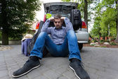 Upset man and car full of luggage bags — Стоковое фото