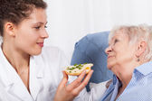 Nurse feeding elderly woman — Stockfoto