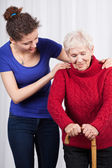 Young woman helping elderly lady — Foto Stock