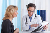 Doctor showing patient test results — Stockfoto