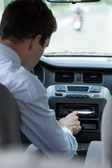 Man changing song in car — Stock Photo