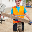 Construction worker holding wooden beam — Stock Photo #50025683