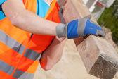 Trabajador obrero sosteniendo una viga de madera — Foto de Stock