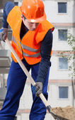 Construction worker digging sand with shovel — Stock Photo