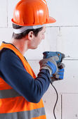 Builder drilling brick wall — Foto Stock