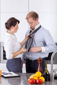 Busy woman tying husband's tie — Stock Photo