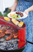 Host serving woman grilled dish — Stock Photo