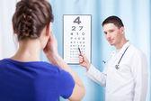 Oculist examining patient — Stock Photo