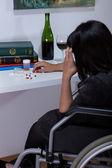 Woman on wheelchair taking drugs — Stock Photo