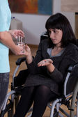 Disabled woman taking medicines — Stock Photo