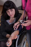 Disabled woman during pressure measurement — Stock Photo