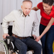 Nurse helps to get up disabled — Stock Photo #50311935