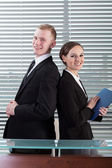 Office workers standing back to back — Stockfoto