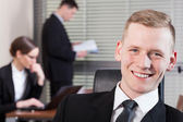Smiling businessman and his co-workers — Stockfoto