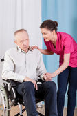 Nurse caring about disabled man — Stock Photo