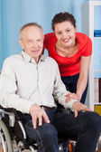 Smiling disabled man and nurse — Stock Photo