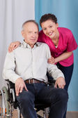 Nurse standing by the disabled in a wheelchair  — Stock Photo