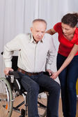 Nurse helps to get up disabled — Stock Photo