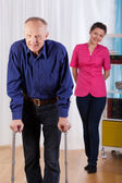 Nurse watches as disabled trying to walk — Stock Photo