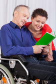 Disabled and a nurse reading a book together — Stock Photo