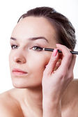 Woman making make-up using eyeliner — Stok fotoğraf