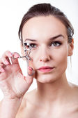 Beautiful girl using eyelash curler — Stok fotoğraf